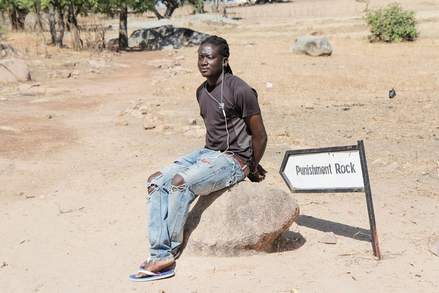 A tour guide at the Pikoro slave camp in Ghana's Upper East Region demonstrates the use of the Punishment Rock; slaves who didn't submit were tied to the rock and left in the sun to die. Half a million new captives from Burkina Faso and Mali were held at this camp.