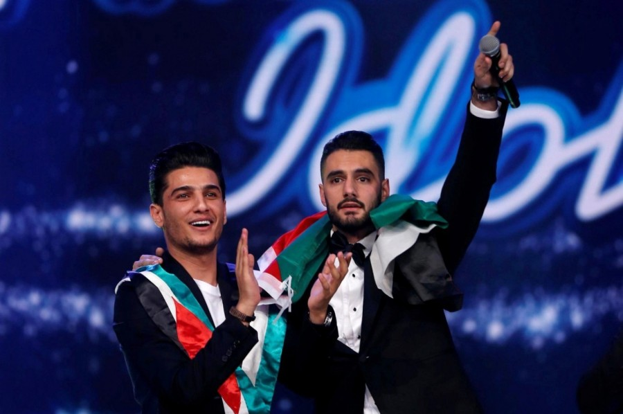 "A Palestinian Christian, Yacoub Shaheen (right), has won the televised, wildly popular singing contest ""Arab Idol,"" prompting joy throughout Palestine, especially in his hometown, Bethlehem. When his name was announced Saturday night he wrapped himself in a Palestinian flag, sang a patriotic song and was joined onstage by a previous winner, Mohammed Assaf of the Gaza refugee camp, now one of the biggest stars in Arabic music. (Reuters)"